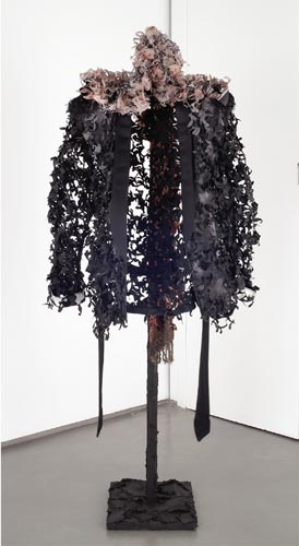 """One Bitch (Tarred and Feathered) 2006 Smoking jacket, scarf, tar, coat tree, 68"""" x 28' x 24"""".  In Twenty Bitches (Tarred and Feathered), I cut along the contours of the pattern in a twenty paisley smoking jackets, reducing this silky symbol of power to a mass of feathery tatters that borders on disintegration. The work, like Fatigue, 2004 (see Underbush), deconstructs the smoking jacket and the inherent power relationship they represent, and hangs them out to dry."""