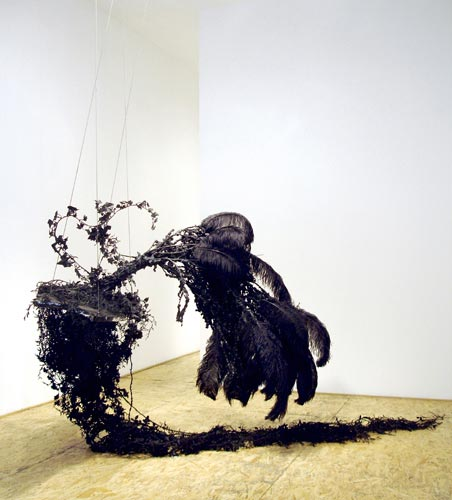 """The Swing, Tar, ostrich feathers, steel cable, mirrored plexi, wood. 56"""" x 48"""" x 96"""". Installation view at Thierry Goldberg Gallery, New York."""